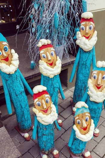 Group of happy handmade wooden dwarfs standing on the street as christmas decoration