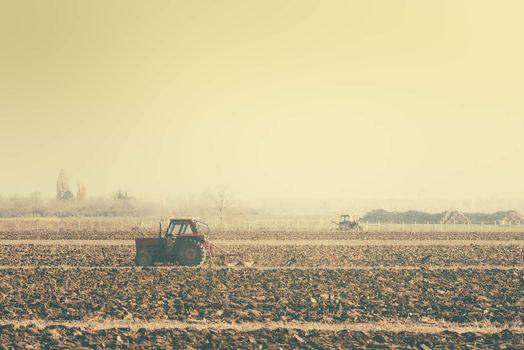 Retro toned tractors on arable field