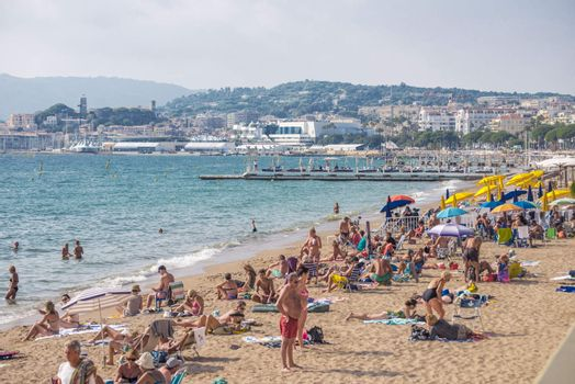 Cannes, France - September 27, 2013: People on the beach in Cannes.  The famous beach on the Croisette, known for its cinema festival. People are sun bathing, swiming and resting 8 mounth in the year.