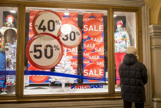 Retail shop window with model mannequins and sale sign.