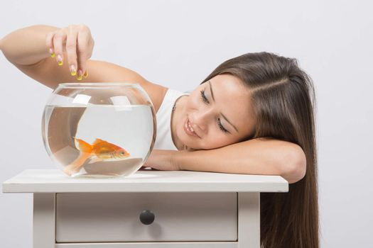 A young girl looks at a goldfish in a fishbowl and feeds her