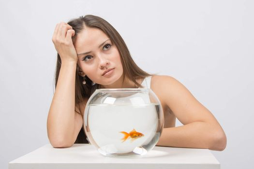 Thoughtful young girl looking at goldfish in a fishbowl