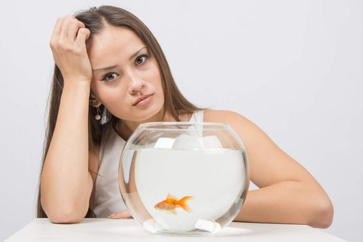 Upset young girl sitting next to the fishbowl