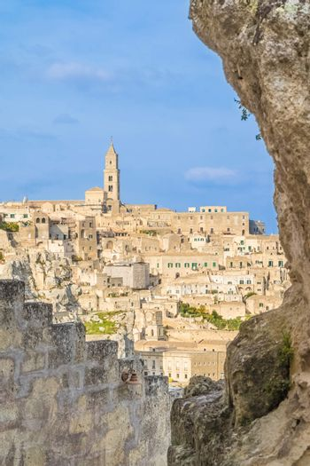 view of typical stones (Sassi di Matera) and church of Matera UNESCO European Capital of Culture 2019 under blue sky