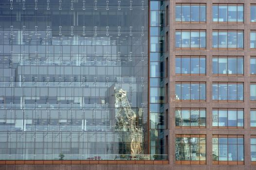 The glass facade of an office and residential complex with reflections in the windows.
