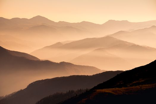 Landscape view of misty mountain hills at sunset with dramatic mood
