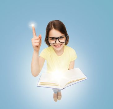 smiling little girl in eyeglasses with book