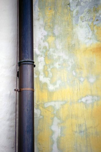A rain of copper pipe is attached to a light wall with traces of water.