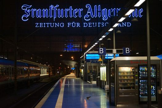 Frankfurt, Germany - November 14, 2015: The main railway station of Frankfurt at night  with a large neon sign of the FAZ newspaper and drink vending machines on November 14, 2015 in Frankfurt.