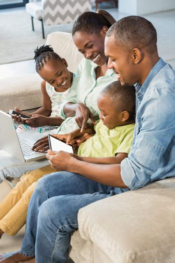 Happy family using technology together in living room
