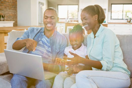 Happy family using laptop on the couch in living room