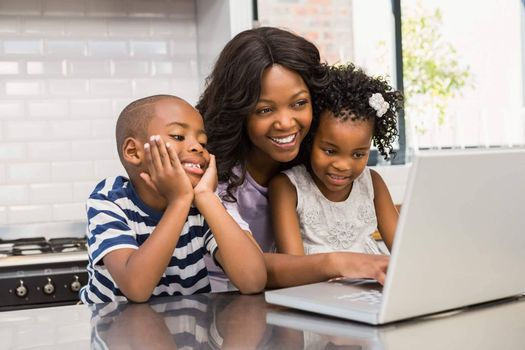 Mother and children using laptop in the kitchen
