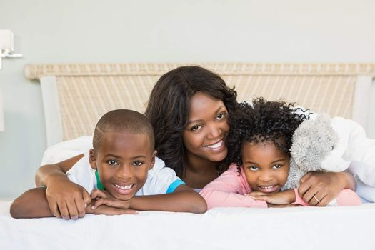 Mother and children lying on bed at home