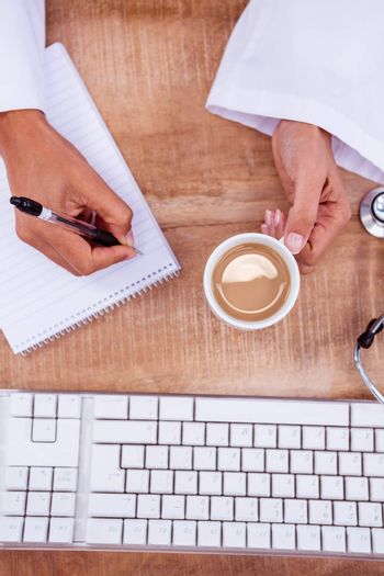 Doctor holding pen and hot beverage