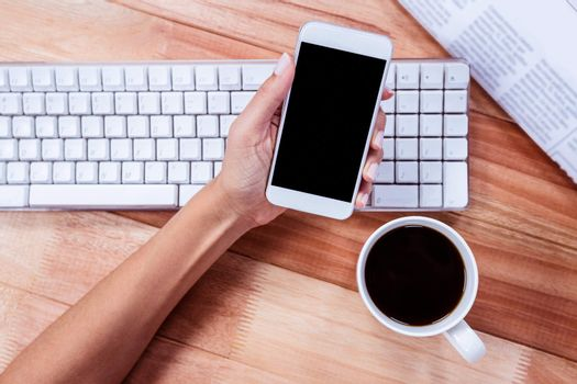Businesswoman holding hot beverage and smartphone
