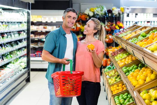 Happy couple talking in the supermarket