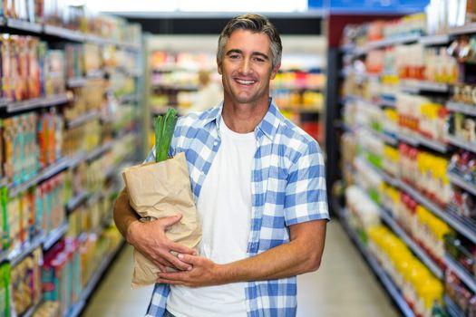 Smiling man holding grocery bag