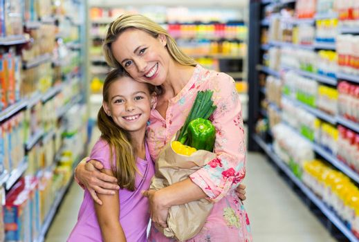 Smiling mother and daughter with grocery bag