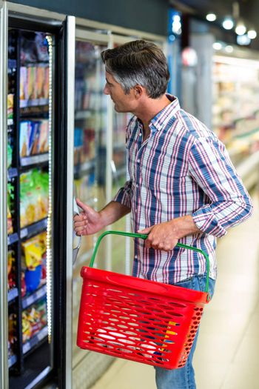 Man opening supermarket fridge