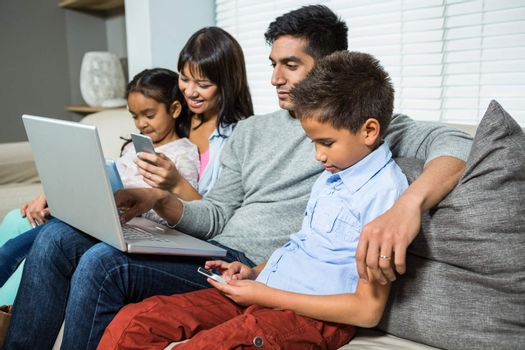 Family sitting on the sofa and using technology
