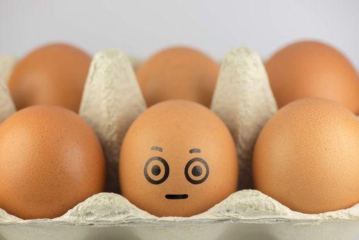 Egg with a face in a egg carton