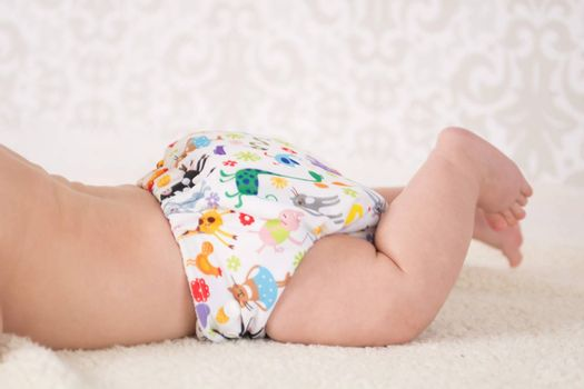 Close-up on a reusable white nappy with colorful animals pattern