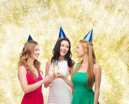 drinks, holidays, people and celebration concept - smiling women in party hats with glasses of sparkling wine over yellow lights background