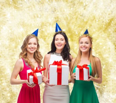 presents, holidays, people and celebration concept - smiling women in party caps with gift boxes over yellow lights background