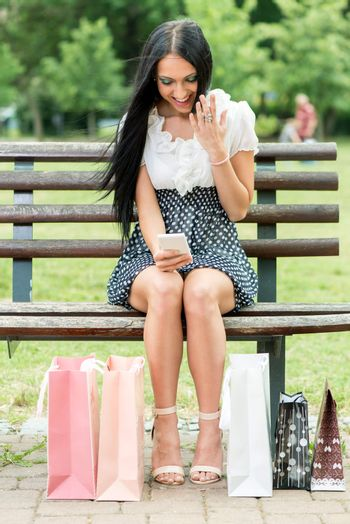 Cheerful girl after shopping with many shopping bags sitting on bench in the park and looking at smart phone.