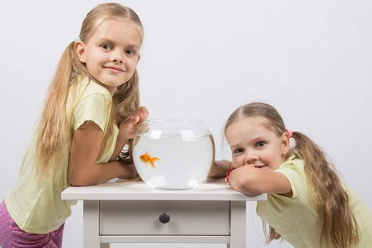Two girls have a small fishbowl with goldfish