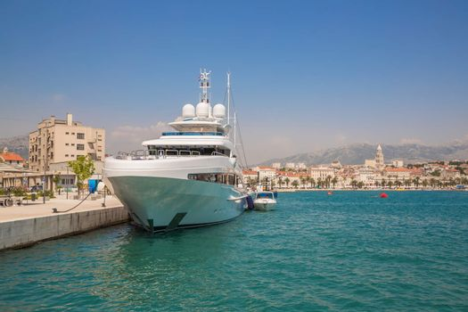 Large yacht at the pier on the background of the coastal town. Split, Croatia.