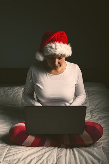 Lonely woman browsing internet on Christmas eve