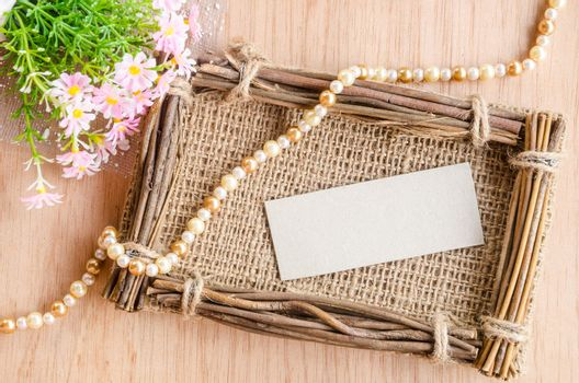 Blank Tag on sack photo frame with flower on wooden background.
