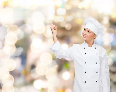 smiling female chef pointing finger to something