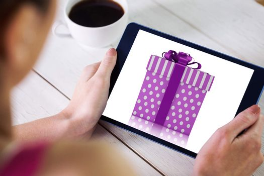 Woman using tablet pc against purple and silver gift box