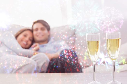 Couple resting on a couch with flutes of champagne against colourful fireworks exploding on black background