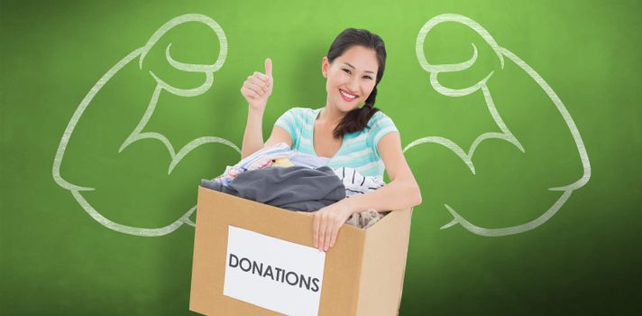 Woman with clothes donation gesturing thumbs up against green chalkboard