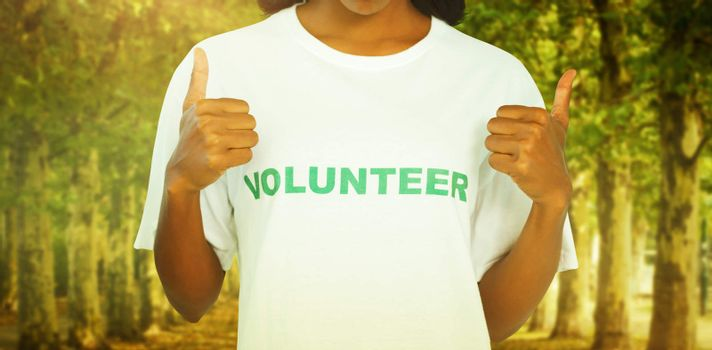 Woman wearing volunteer tshirt and giving thumbs up against walkway along lined trees in the park
