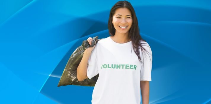 Team of volunteers picking up litter in park against abstract blue design