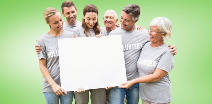 Composite image of happy volunteer family holding a blank