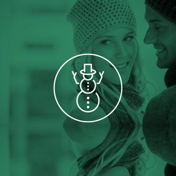 Couple in warm clothing hugging against snowman