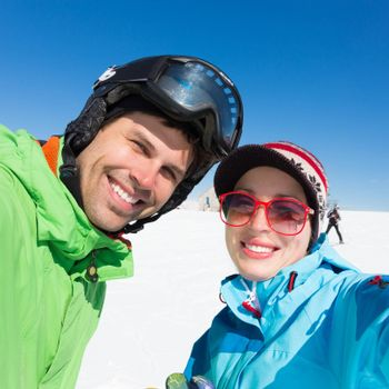 Selfie of couple skiers on winter vacations in the Alp mountains, Triglav natural park, Vogel, Slovenia.