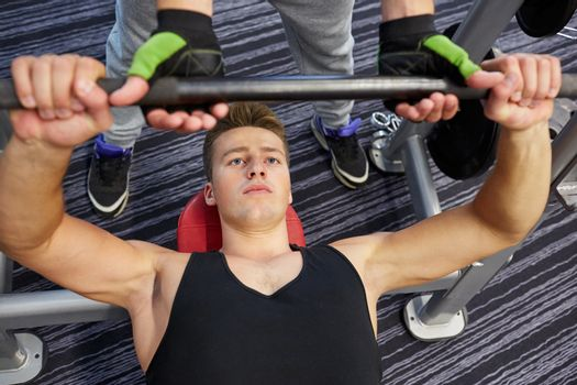 men doing barbell bench press in gym