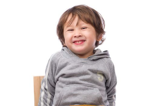 A cute 3 year old boy with a happy expression on a white background.