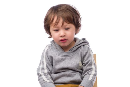 A cute 3 year old boy with a sad expression on a white background.
