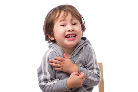 A cute 3 year old boy with a happy expression shivering and pretending to be cold on a white background.