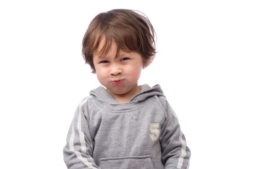 A cute 3 year old boy with an angry expression on a white background.