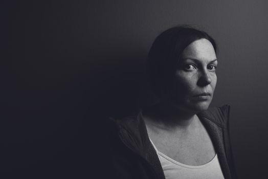 Intense low key portrait of pensive sad woman