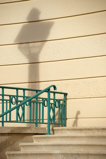 A newly renovated building wall with a lantern shadow and parts of a Stairs and Railings.