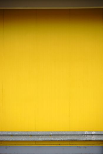 A guard rail is bolted to a smooth yellow wall.